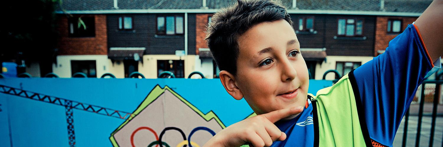 young boy points in front of graffiti featuring olympics logo