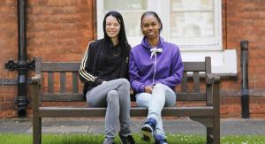 Two young people sitting outside St Basils accommodation