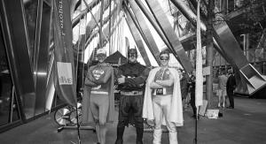 three men dressed as superheroes pose in front of skyscraper