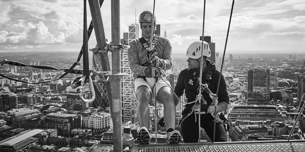 two men abseil off roof of skyscraper