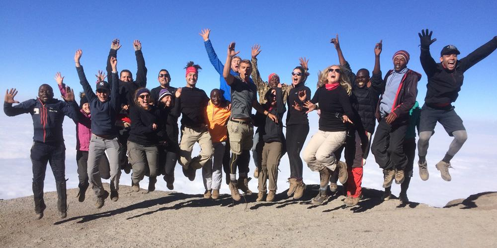 Knight Frank team jumping and cheering on Kilimanjaro