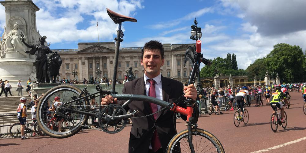 Victorious Ride London participant in a suit holding his Brompton