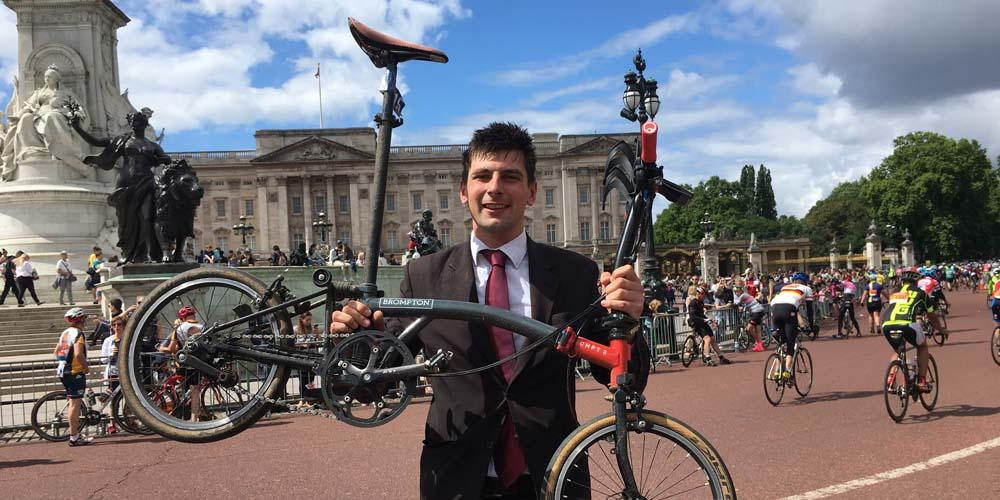 Matthew Tatlock holding Brompton up in front of Buckingham Palace
