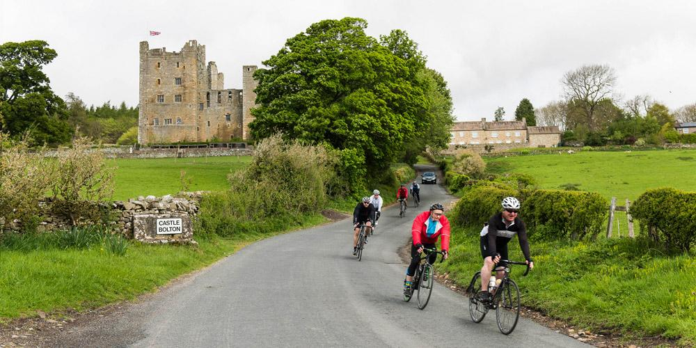 cyclists ride in front of castle