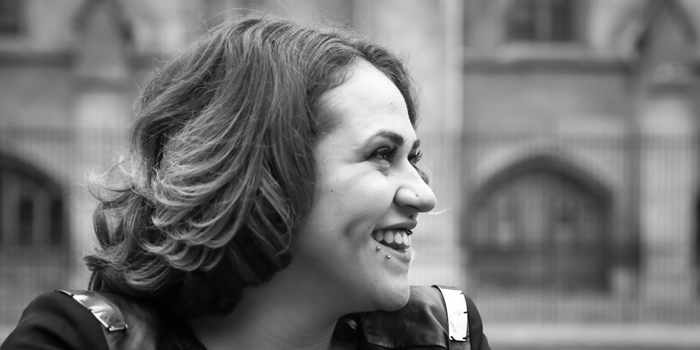 black and white photo of young woman smiling in front of house of commons