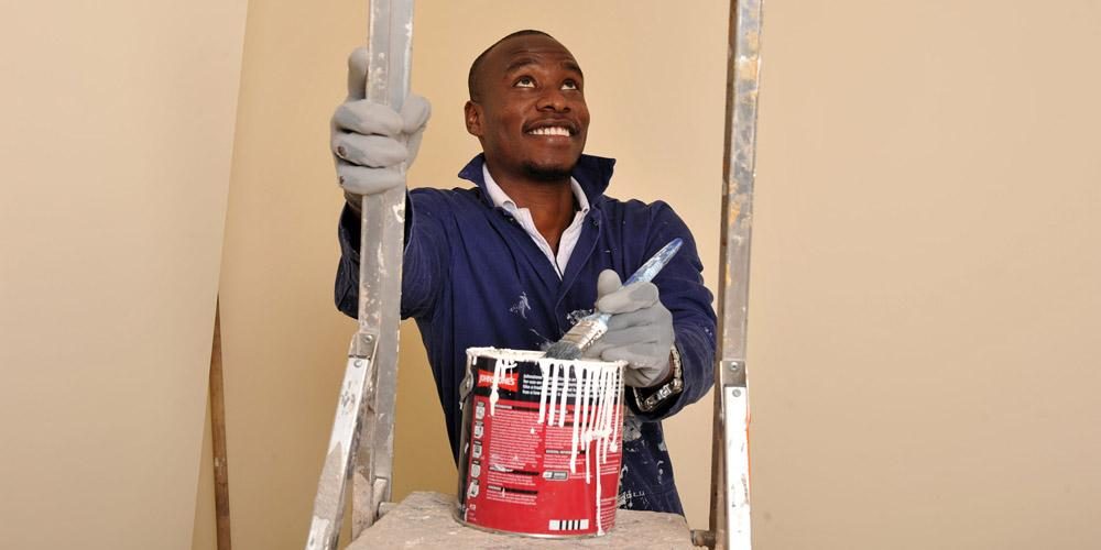 young man stands on ladder with paintbrush and tin of paint