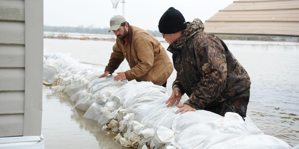 two men move sand bags to stop flooding