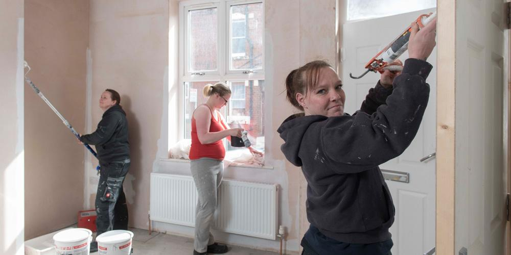 young women decorating room in house