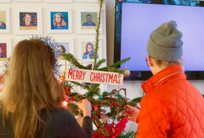 Young people decorating Christmas tree