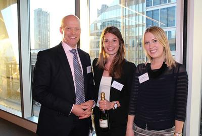 Property professionals celebrating award besides window