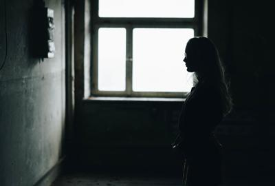 Young woman standing in derelict home