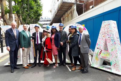 Group of important guests in front of large colourful YMCA letters