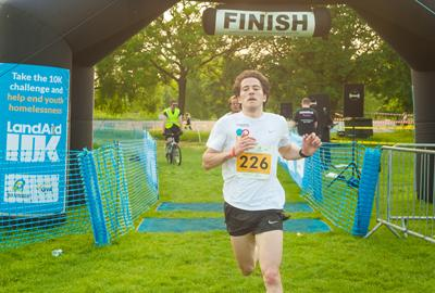 LandAid 10K winner crossing finish line