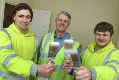 three men holding paintbrushes