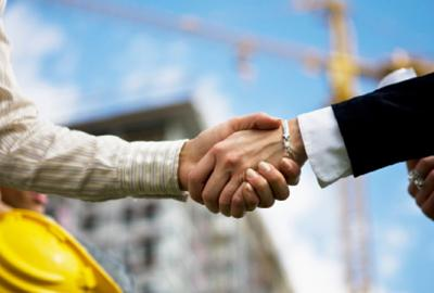 two men shake hands on building site