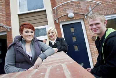 three young people lean on garden wall