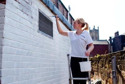 young woman on ladder painting house
