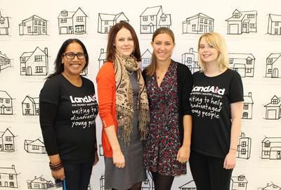four women stand in front of wall covered in pictures of houses
