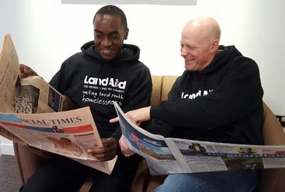 two men sit on a sofa reading newspapers and laughing