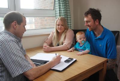 family sitting at table with support worker